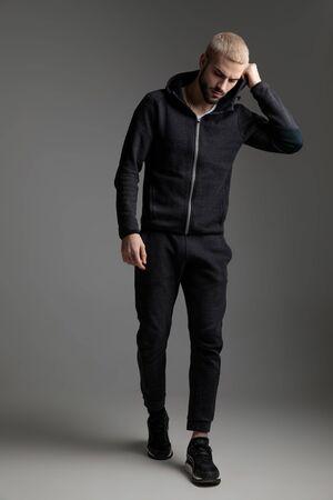 Rubio casual hombre vestido con chándal caminando mientras se fija la capucha y mirando hacia abajo triste sobre fondo gris de estudio