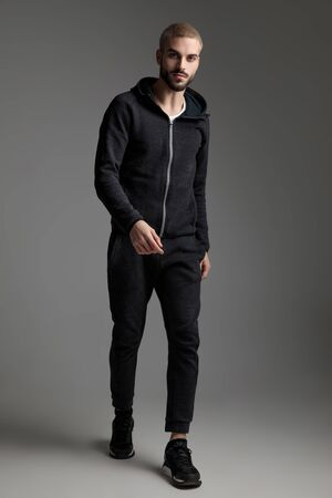 Atractivo hombre casual vestido con chándal caminando y mirando a la cámara sobre fondo gris de estudio