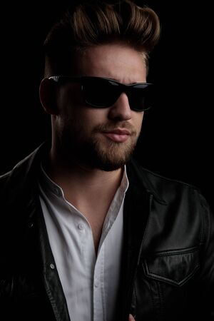 close up of a gorgeous casual man wearing sunglasses and looking away on black studio background