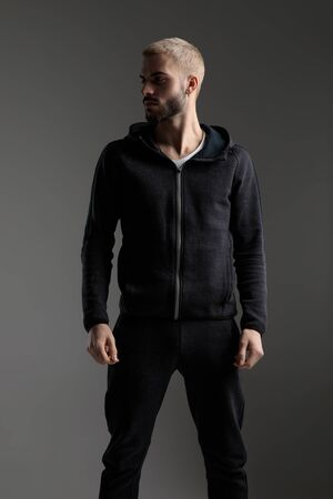 handsome casual man wearing tracksuit standing with hands loose and looking aside serious on gray studio background