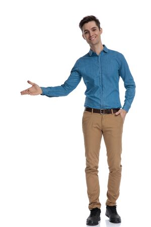 happy young man wearing blue shirt smiling and presenting to side, standing isolated on white background, full body