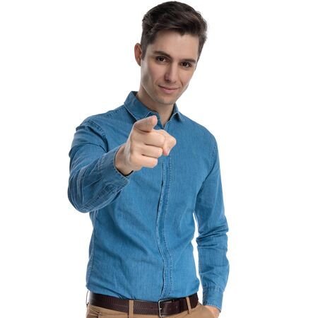 confident young man in blue shirt smiling and pointing finger, standing isolated on white background, portrait