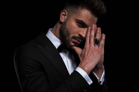 vue latérale d'un homme d'affaires portant un smoking noir debout et regardant la caméra avec les mains jointes sur fond de studio noir