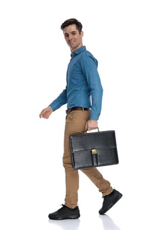 side view of young man smiling and holding suitcase, walking isolated on white background, full body