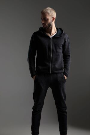 good looking casual man wearing tracksuit standing with hands in pocket and looking aside serious on gray studio background