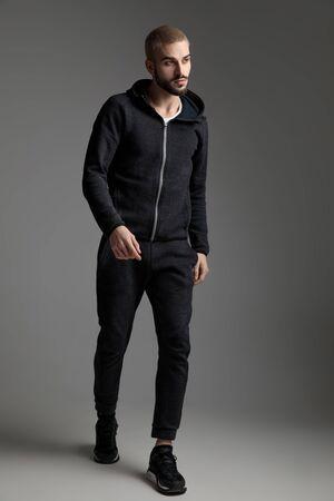 Hombre casual vestido con chándal caminando y mirando a otro lado pensativo sobre fondo gris de estudio