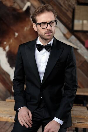 Concerned fashion model looking away while wearing tuxedo and glasses, sitting on a table on coffeeshop background Stock Photo