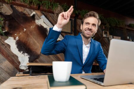 Positive businessman laughing and greeting while sitting at a desk with a book, coffee cup and laptop on it, on coffeeshop background Reklamní fotografie