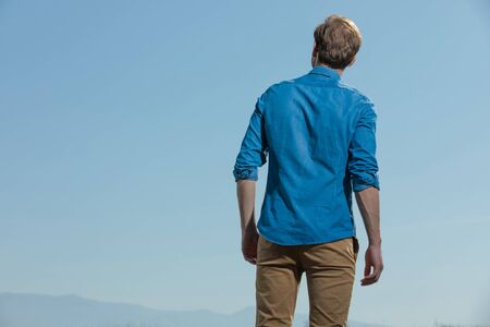 rear view of a casual man standing relaxed with hands loose and looking away pensive outside on blue sky