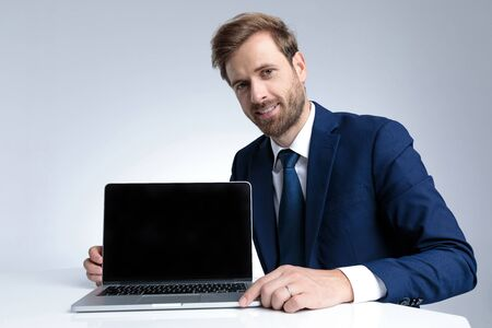 Handsome businessman presenting his laptop while wearing a blue suit and sitting on gray studio background
