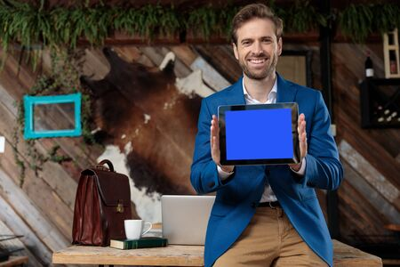 Cheerful businessman laughing and presenting a blank tablet while leaning on a table with a laptop, briefcase, coffee cup and book on coffeeshop background