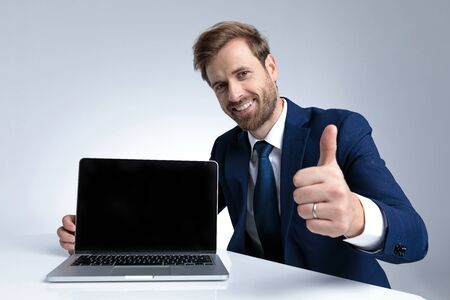 Cheerful businessman giving a thumbs up and presenting his laptop while wearing a blue suit and sitting on gray studio background 版權商用圖片