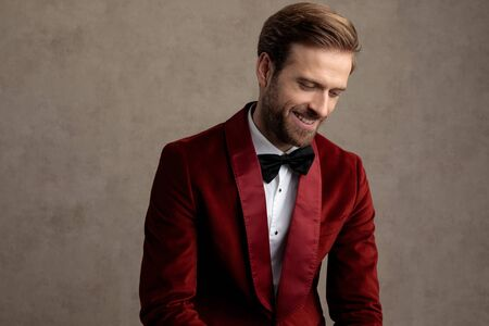 Happy bridegroom looking down and laughing while wearing tuxedo and sitting on a stool on brown studio background
