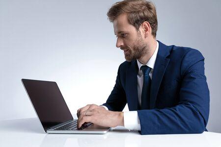 Seitenansicht eines gutaussehenden Geschäftsmannes, der auf seinem Laptop arbeitet und schreibt, während er einen blauen Anzug trägt und auf grauem Studiohintergrund sitzt