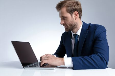 Zijaanzicht van een knappe zakenman die op zijn laptop werkt en schrijft terwijl hij een blauw pak draagt en op een grijze studioachtergrond zit