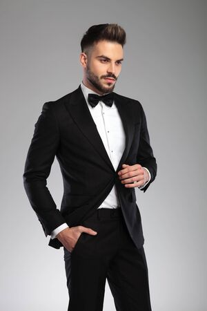 Eager groom looking away with his hand in his pocket while wearing tuxedo, walking on gray studio background