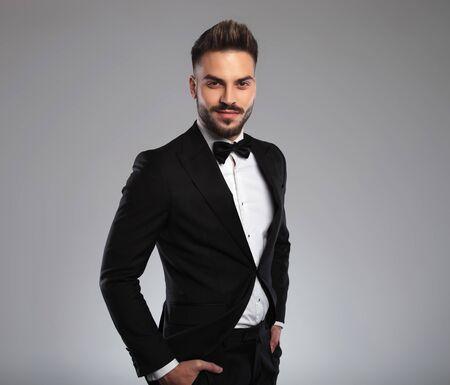 Selbstbewusstes Model, das seine Hände in den Taschen hält und lächelt, während es Smoking trägt und auf grauem Studiohintergrund geht Standard-Bild