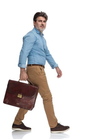 Side view of a positive casual man holding his briefcase while moving on white studio background