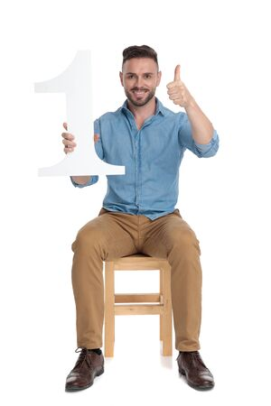 young casual guy holding number one sign and making thumbs up sign, sitting isolated on white background, full body