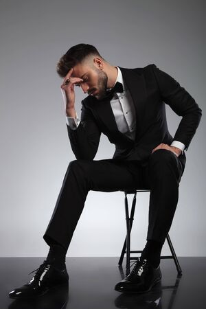Thoughtful groom holding his hand on his forehead and wondering while wearing tuxedo, sitting on a chair on gray studio background
