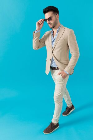 cool fashion model fixing sunglasses and walking on blue background, full body