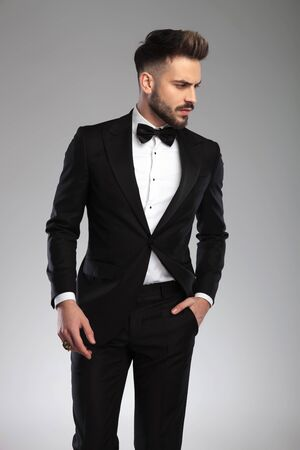 Curious model looking away adn wondering, holding his hand in his pocket while wearing tuxedo, walking on gray studio background