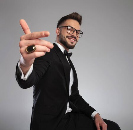 Happy groom inviting and smiling while wearing tuxedo and sitting on a stool on gray studio background