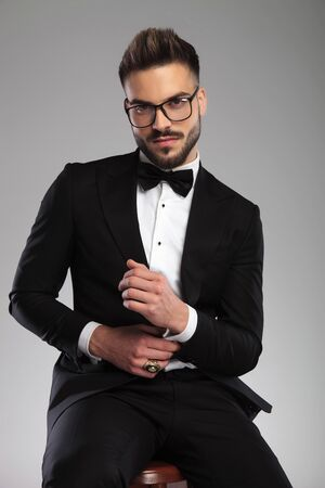 Tough groom adjusting his sleeve while wearing glasses and tuxedo, sitting on a stool on gray studio background 스톡 콘텐츠