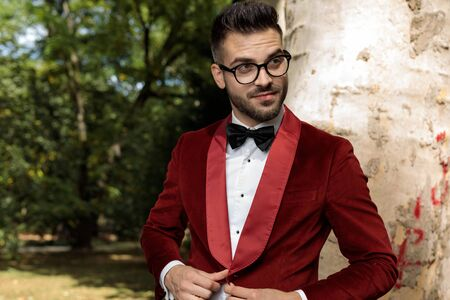charming businessman wearing red tuxedo standing against tree and opening his coat happy outside in park