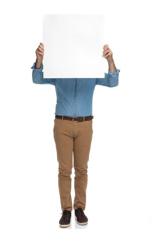 Old casual man holding an empty billboard over his face while standing on white studio background