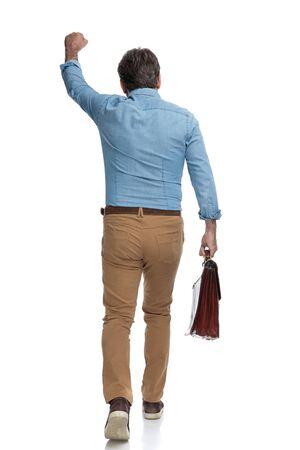Rückansicht eines positiven zufälligen Mannes, der seine Aktentasche feiert und hält, während er auf weißen Studiohintergrund tritt