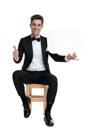 jeune homme souriant tenant une bulle de dialogue et faisant signe de pouce levé, souriant et assis isolé sur fond blanc, corps entier