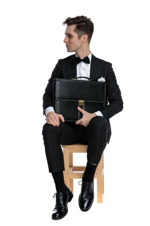 serious fashion model holding suitcase and looking to side, sitting isolated on white background, full body