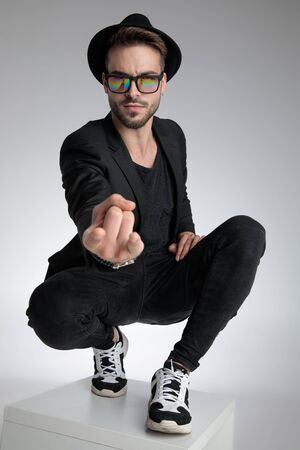 cool dramatic man holding hand in a fashion pose, wearing hat and sunglasses, crouching on grey background