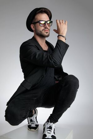 sexy young man holding elbow in a fashion pose, wearing hat and sunglasses on grey background Foto de archivo