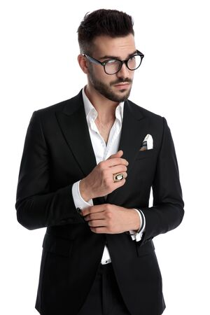 handsome formal business man wearing black tuxedo,eyeglasses,ring standing and fixing his sleeve while looking away pensive against white studio background