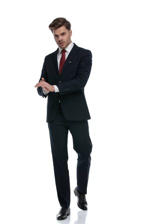 elegant young businessman in suit rubbing palms and walking isolated on white background, full body