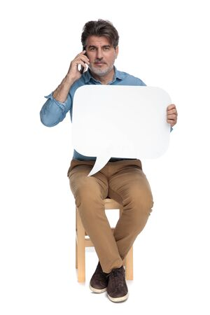 Confident casual man talking on phone and holding speech bubble while sitting on a chair on white studio background