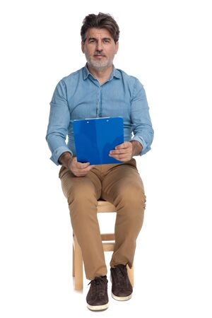 Serious looking casual man holding a clipboard while sitting on a chair on white studio background 免版税图像