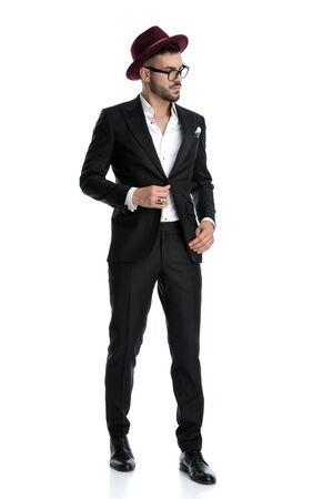 Seitenansicht eines charmanten formellen Geschäftsmannes mit burgunderfarbenem Hut, der beiseite steht und zur Seite schaut, während er die Jacke ernsthaft vor weißem Studiohintergrund fixiert Standard-Bild