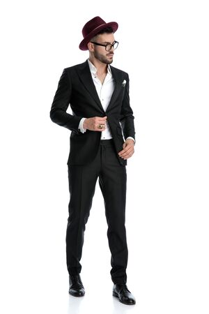 zijaanzicht van een charmante formele zakenman met een bordeauxrode hoed die staat en opzij kijkt terwijl hij een serieus jasje repareert tegen een witte studio-achtergrond Stockfoto