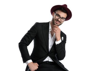 charming formal business man wearing burgundy hat sitting and touching chin while staring at camera seductive against white studio background