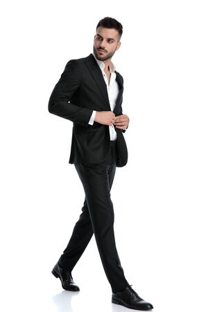 side view of a charming formal business man wearing black tuxedo walking one way and looking the other while fixing jacket confident against white studio background