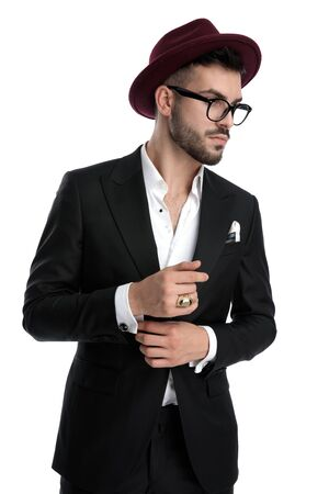 formal business man wearing burgundy hat standing and fixing sleeve while looking aside pensive against white studio background