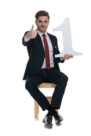 young elegant businessman holding number one sign and making thumbs up sign, sitting isolated on white background, full body
