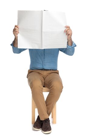 Old casual man covering his face with a newspaper while sitting on a chair on white studio background