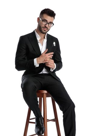 charming formal business man wearing black tuxedo and glasses sitting and rubbing hands serious against white studio background