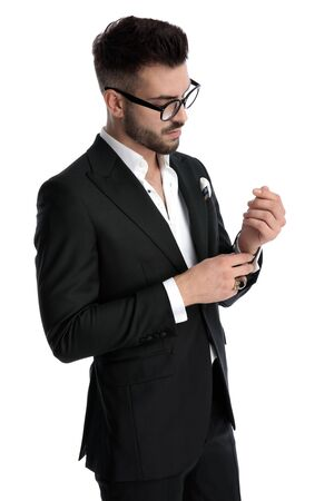 side view of a beautiful formal business man wearing black tuxedo,eyeglasses,ring fixing and looking at sleeve serious against white studio background