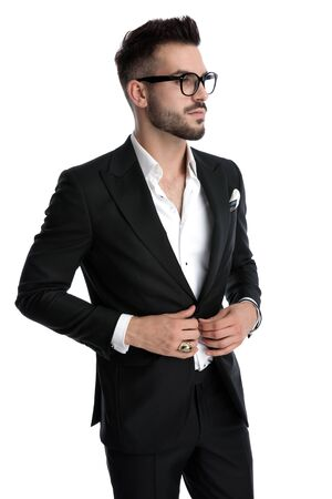 young formal business man wearing black tuxedo,eyeglasses,ring standing and looking aside while fixing jacket serious against white studio background Stock Photo