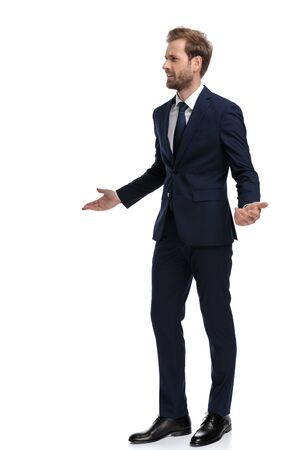 young businessman in navy blue suit looking confused and asking for explanations, standing isolated on white background, full body